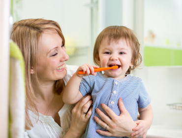 mother teaching son child teeth brushing in bathroom