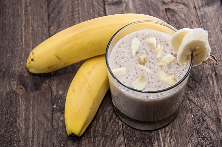 Banana Smoothie with fresh fruits on wooden background