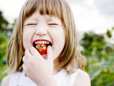 Young Girl(5-6) biting into cherry tomato