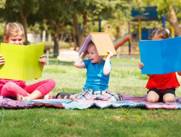 Happy children of three sitting with books