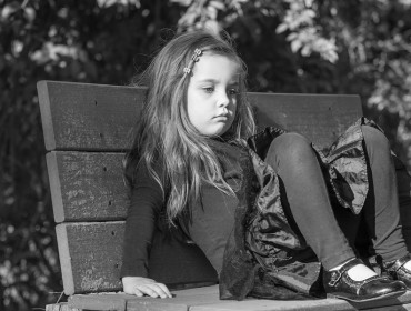 tired or bored little girl sitting on a bench in a park, black and white image