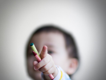 Toddler holding crayons and pointing index finger